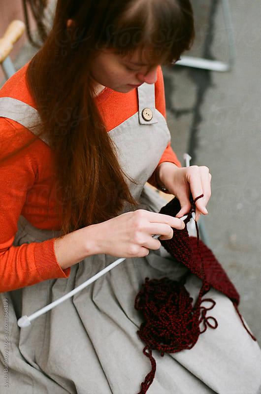 Yong woman knitting outdoors by Lyuba Burakova for Stocksy United