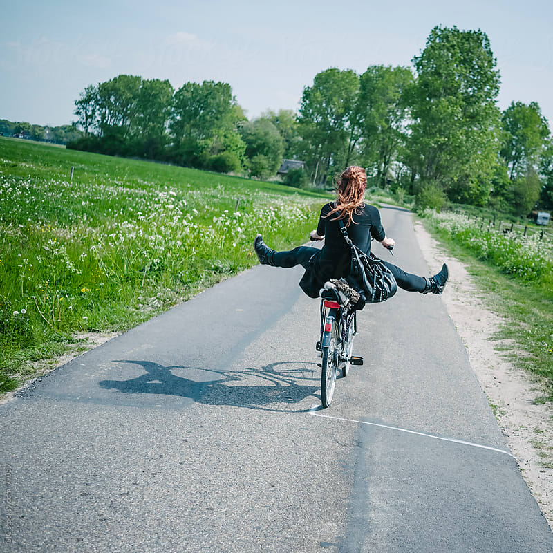 Playful girl rides a bicycle in the green country by GIC for Stocksy United