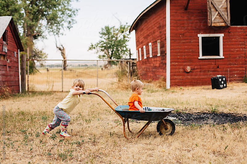 Big sister pushes her little brother in a wheelbarrow on a farm. by Jessica Byrum for Stocksy United