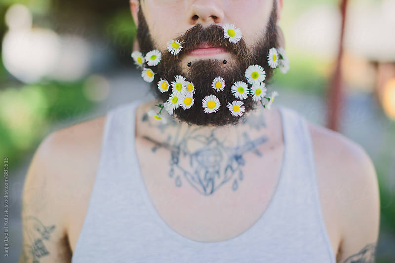 Young tattooed man with flowers in beard by Sanja (Lydia) Kulusic for Stocksy United