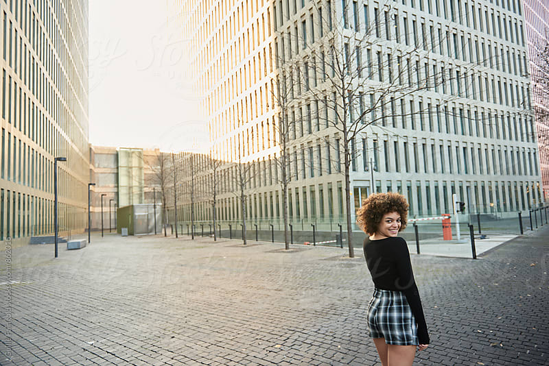 Young woman with afro looking at camera over  shoulder by Guille Faingold for Stocksy United