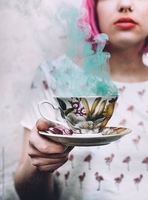 girl holds  a teacup with blue smoke by Thais Ramos Varela for Stocksy United