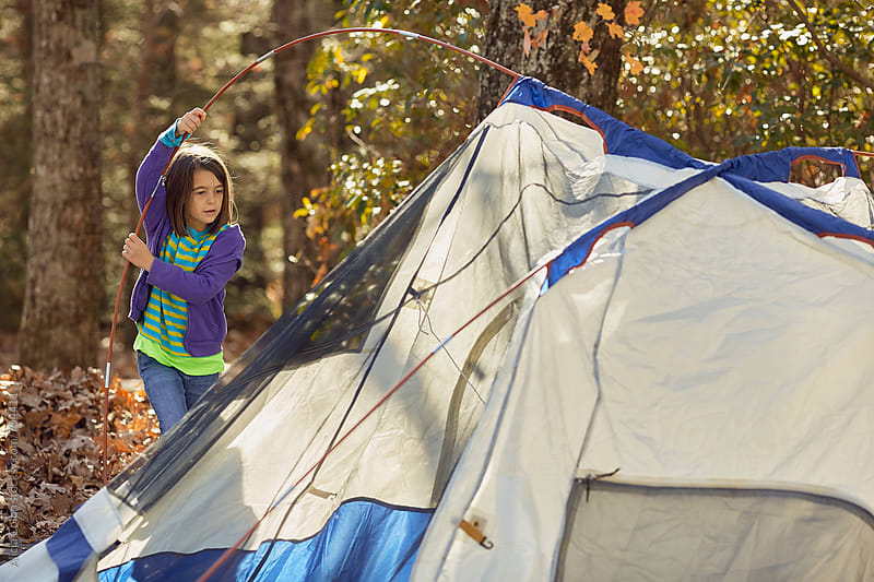 Young girl setting up a tent by Alicja Colon for Stocksy United