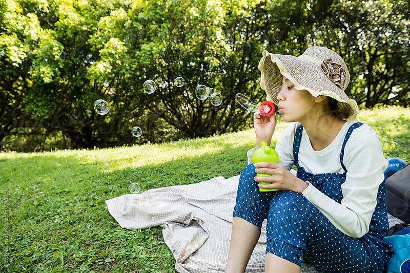 Young woman blowing bubbles on green grass at park by Lawren Lu for Stocksy United