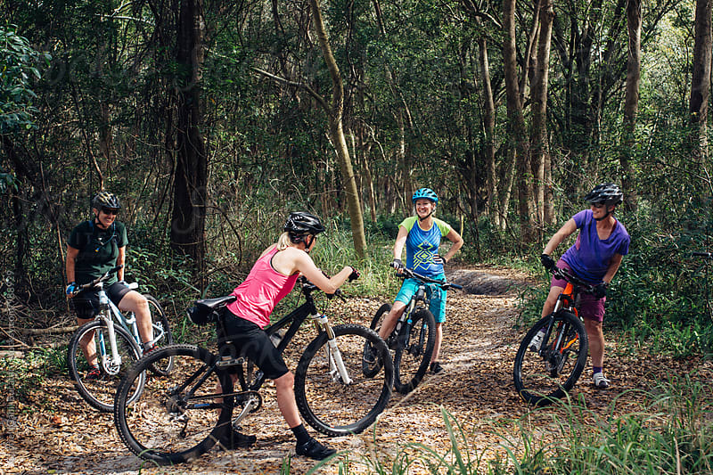 Group of cyclist women taking a rest on a mountain bike trail by Gabriel (Gabi) Bucataru for Stocksy United