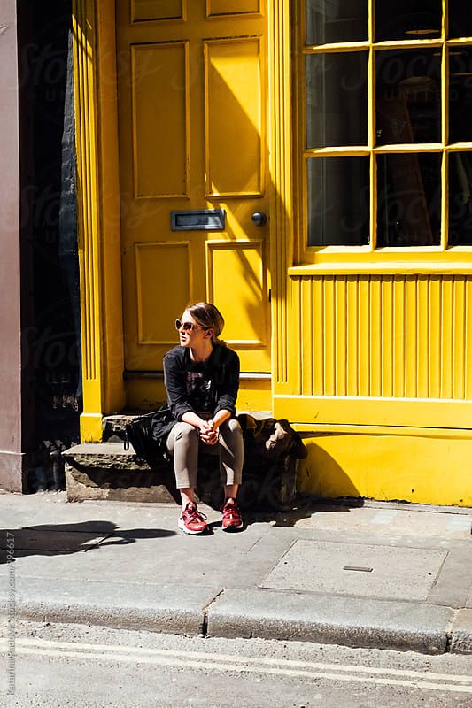 Young Woman Sitting on the Stairs in Front of the Bright Yellow Shop by Katarina Radovic for Stocksy United