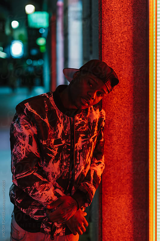 Young Black Man Illuminated by a Red Neon Light by VICTOR TORRES for Stocksy United