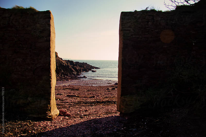 View through a sea defence wall. by Helen Rushbrook for Stocksy United