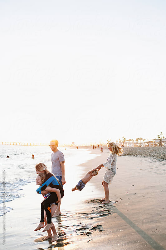 Family giving piggyback rides and playing on beach by Kristin Rogers Photography for Stocksy United