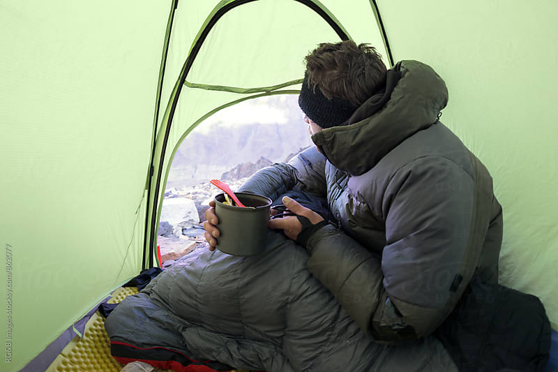 Man eating inside his tent looking out by RG&B Images for Stocksy United