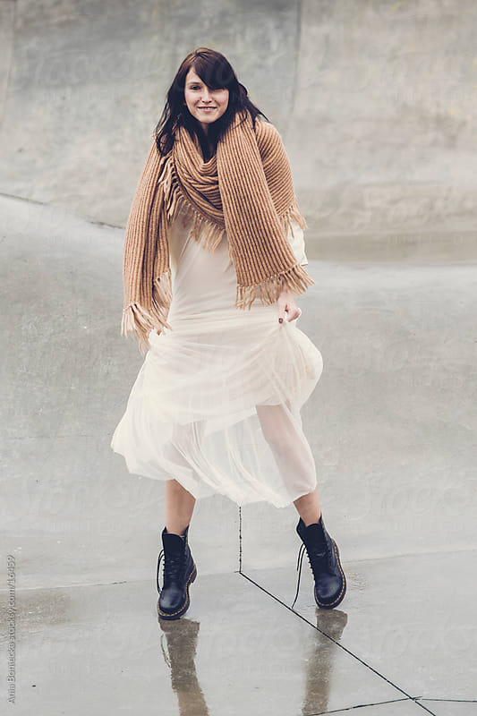 A beautiful young woman dancing in a long dress and combat boots by Ania Boniecka for Stocksy United