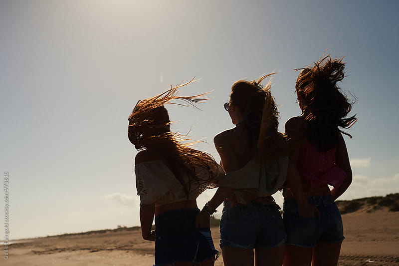 Back view of three friends on road with windy hair by Guille Faingold for Stocksy United