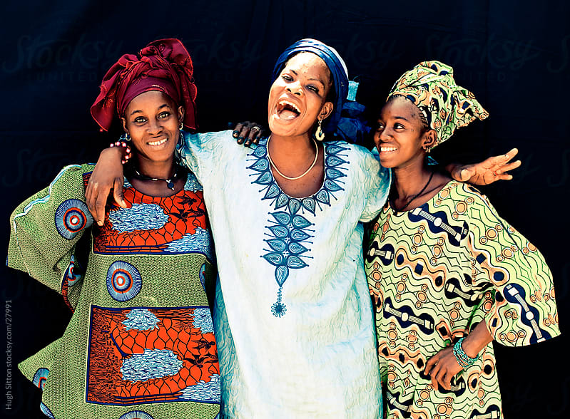 Three happy, smiling female friends hanging out together. Mali by Hugh Sitton for Stocksy United
