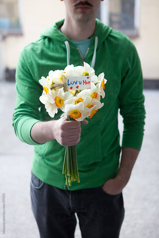 Man holding bouquet of narcissus. by Mosuno for Stocksy United