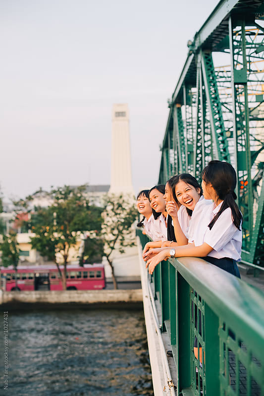 High school girl enjoying on the bridge over river at sunset time in Bangkok by Nabi Tang for Stocksy United