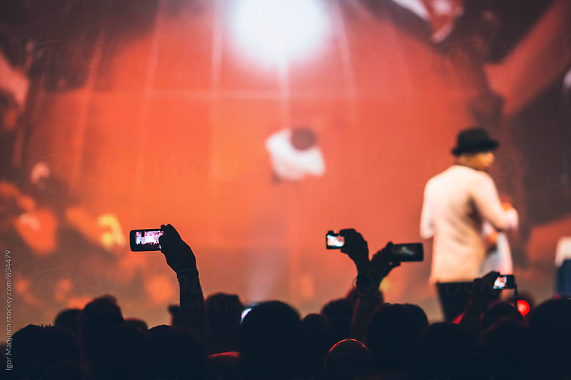 audience with mobile phones,stage,red by Igor Madjinca for Stocksy United