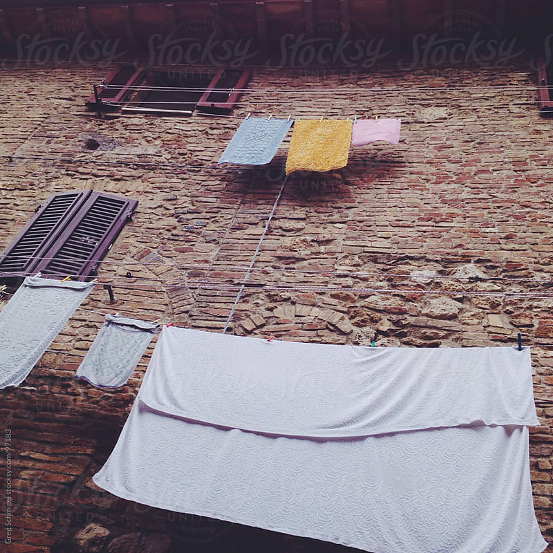 Laundry and linens hung to dry in the fresh air in Italy. by Greg Schmigel for Stocksy United