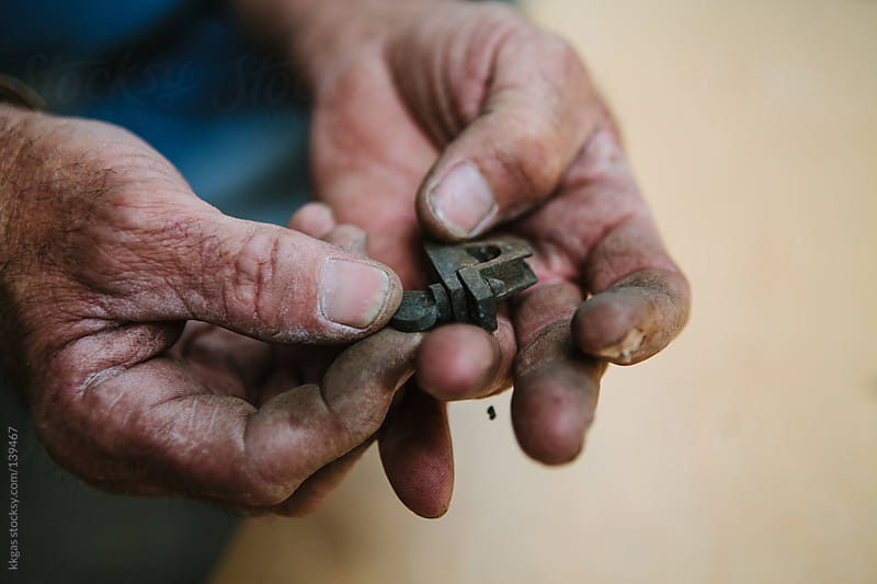 workmans hands holding an antique lock. by kkgas for Stocksy United