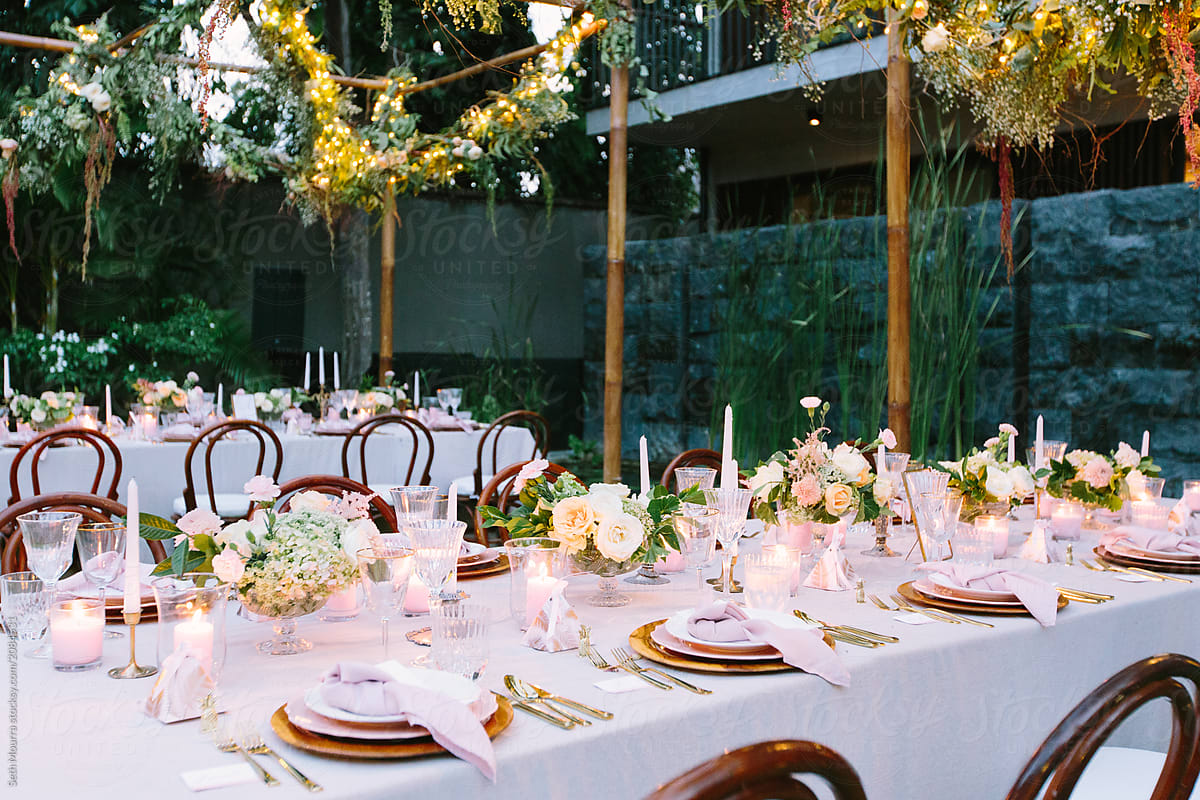Outdoor, tropical wedding reception with hanging greenery garlands ...