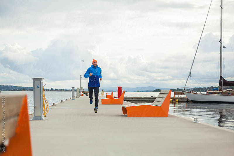 Running by the dock by Jelena Jojic Tomic for Stocksy United