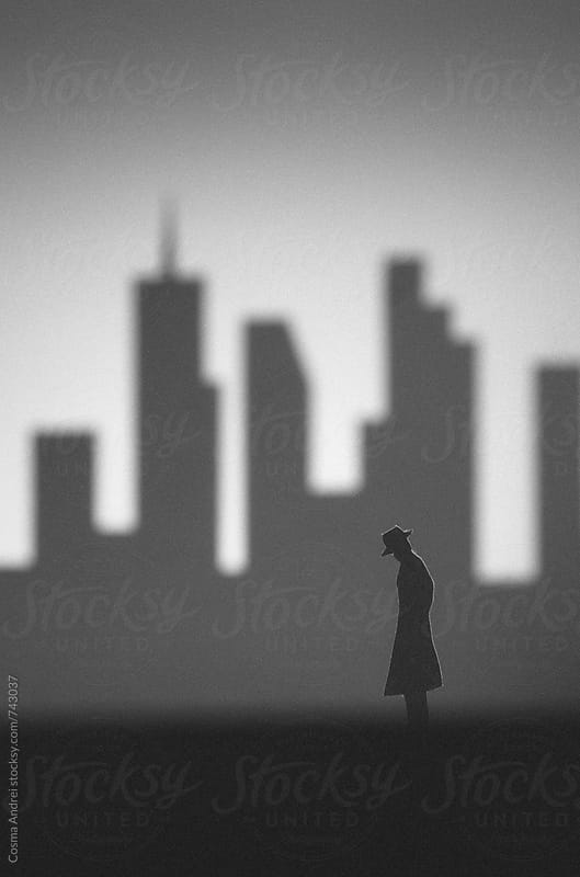 Dark city with silhouette of man detective with skyscrapers by Cosma Andrei for Stocksy United