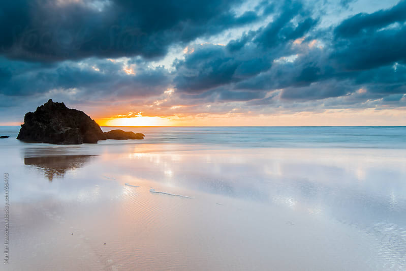 Sunset on a beach in northern Spain with a dramatic sky by Marilar Irastorza for Stocksy United
