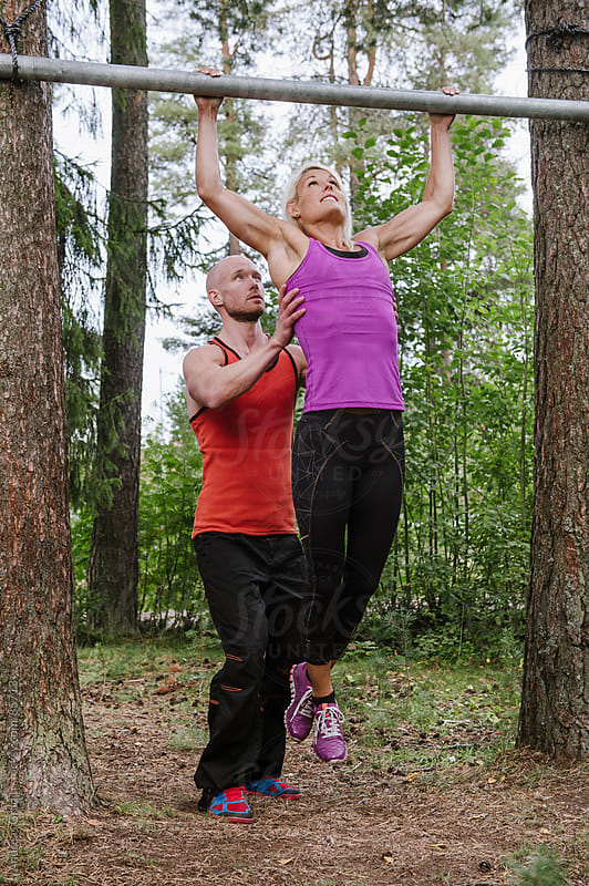 couple doing pullups at workout by Andreas Gradin for Stocksy United