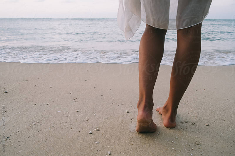 Female legs on a sandy beach. by Marija Savic for Stocksy United