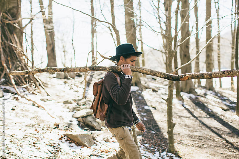 Side view of a mountaineer holding a long branch on the woods. by BONNINSTUDIO for Stocksy United