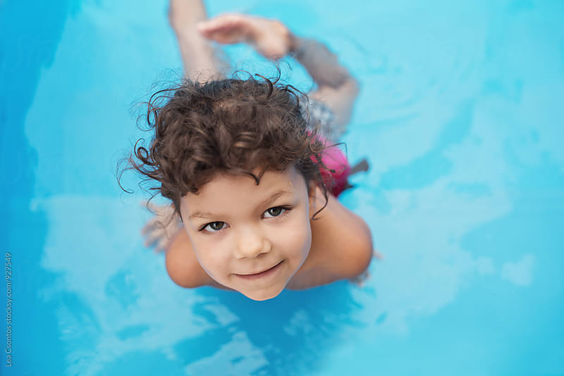 Portrait of a little girl in a swimming pool looking up by Lea Csontos for Stocksy United