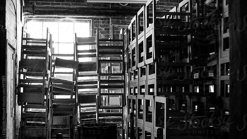 Chairs stacked near windows in a chair woodworking workshop by J Danielle Wehunt for Stocksy United