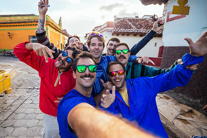 Group of happy friends taking a selfie in a street on their vacation at sunset by Alejandro Moreno de Carlos for Stocksy United