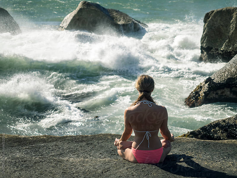 Young woman doing Yoga and meditating on the rocks by the sea by DV8OR for Stocksy United