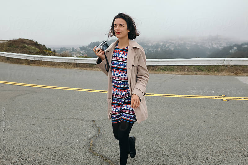 brunette tourist with camera walking across road on top of Twin Peaks lookout by Lucas Saugen for Stocksy United
