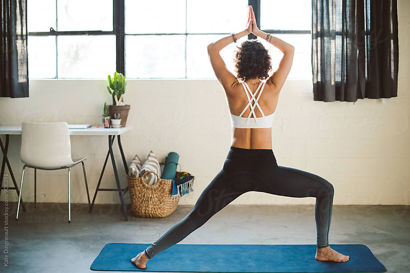 Young fit woman does yoga in her bright city loft. by Kate Daigneault for Stocksy United