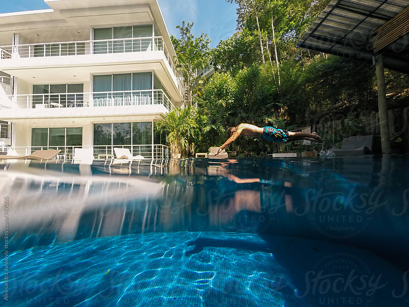 Man jumping in the Swimming Pool at the Tropical Resort by Aleksandra Jankovic for Stocksy United