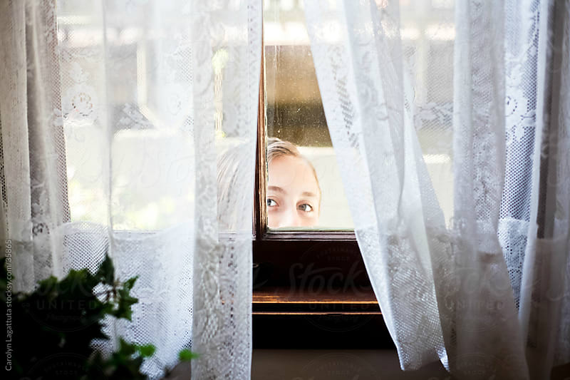 Girl looking into the window from outside. by Carolyn Lagattuta for Stocksy United