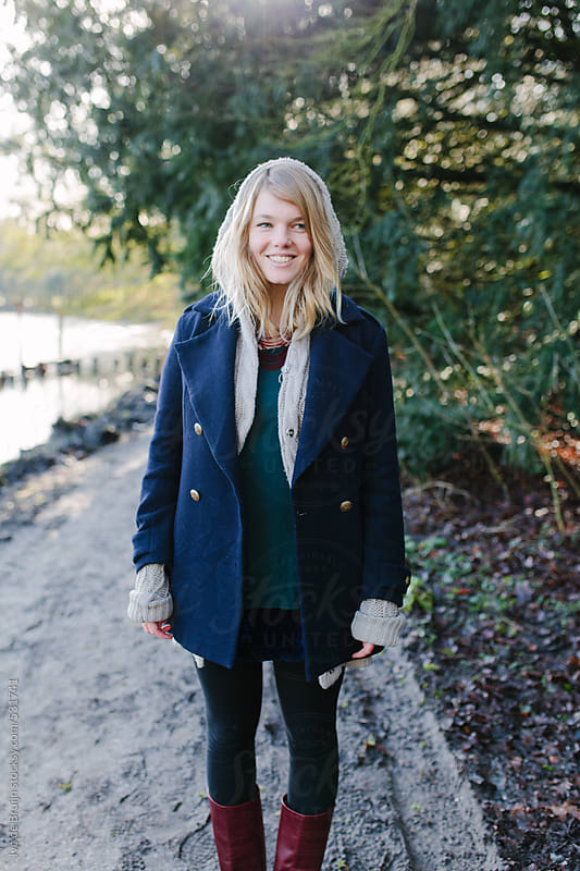 A young white woman laughing and looking at the camera while standing a forest path by Ivo de Bruijn for Stocksy United