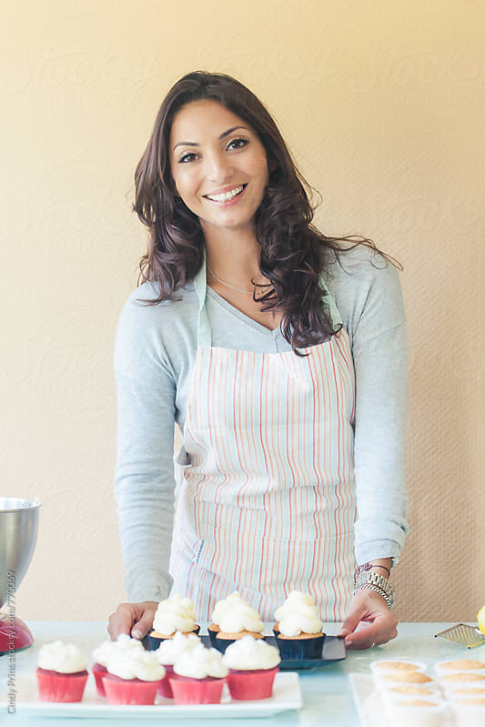 Smiling woman with plates of freshly baked cupcakes by Cindy Prins for Stocksy United