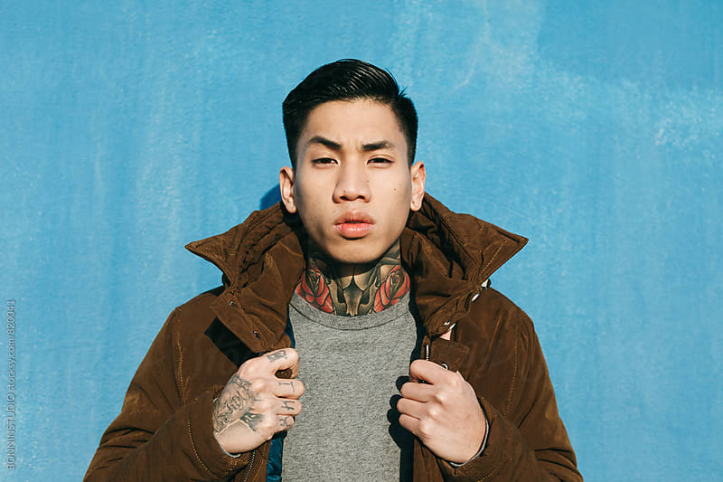 Portrait of an asian tattooed man in front of a blue wall. by BONNINSTUDIO for Stocksy United