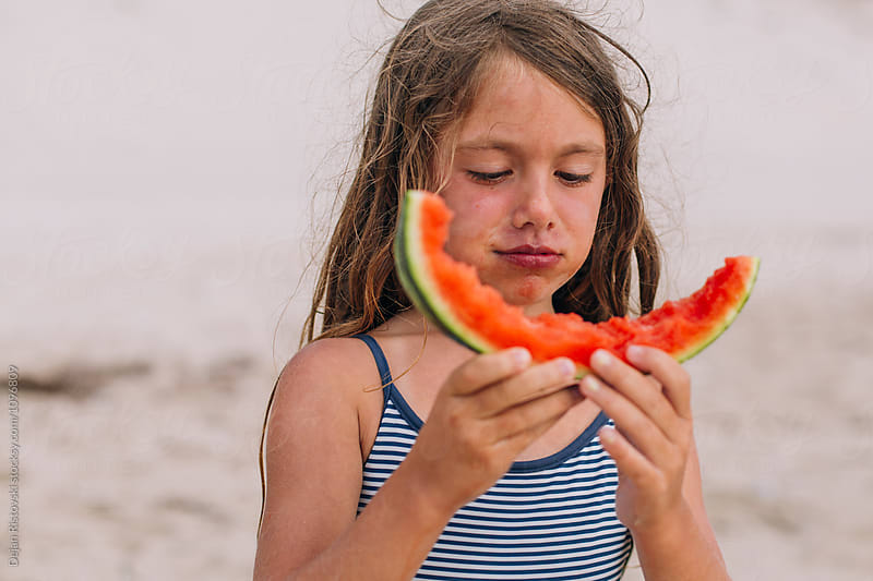 Girl eating slice of watermelon at the beach. by Dejan Ristovski for Stocksy United
