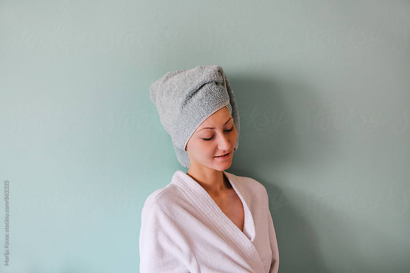 Young woman in a bathrobe and with a towel on her head smiling  by Marija Kovac for Stocksy United