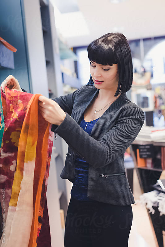Woman looking for a new scarf inside a shop by Mauro Grigollo for Stocksy United