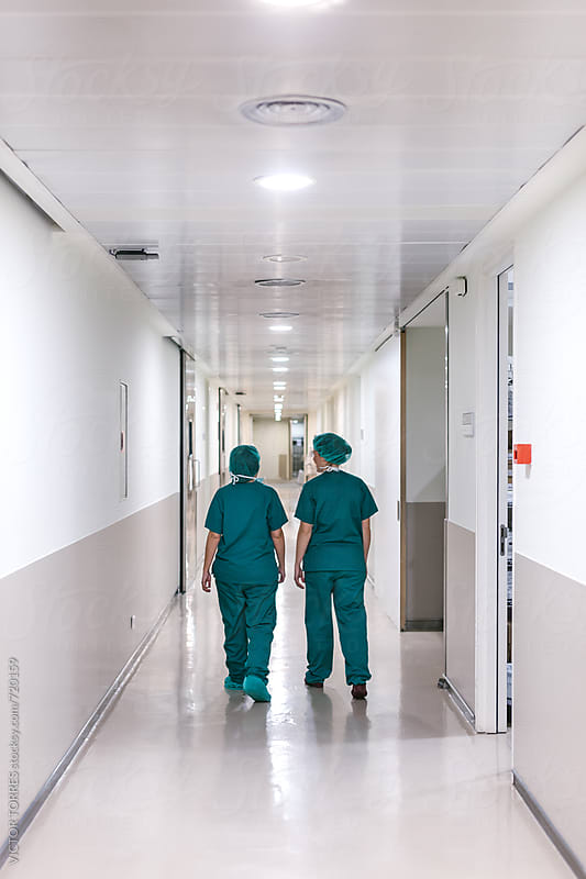Surgeons Walking Through a Hospital Corridor by Victor Torres for Stocksy United