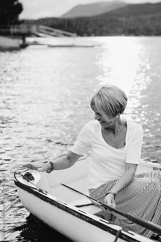 Mature woman sitting in row boat by Rob and Julia Campbell for Stocksy United