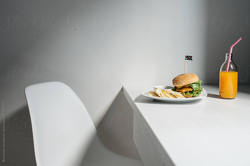 Burger and orange juice on the table by Brkati Krokodil for Stocksy United