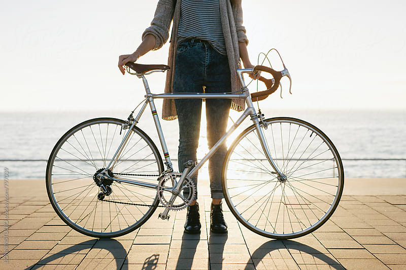 Anonymous woman standing with her vintage bicycle by the sea. by BONNINSTUDIO for Stocksy United