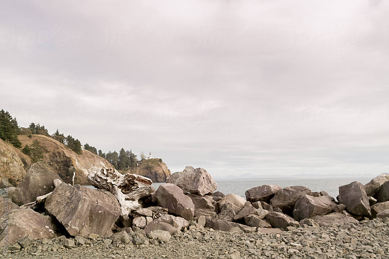 rocky beach with lighthouse by Tod Kapke for Stocksy United