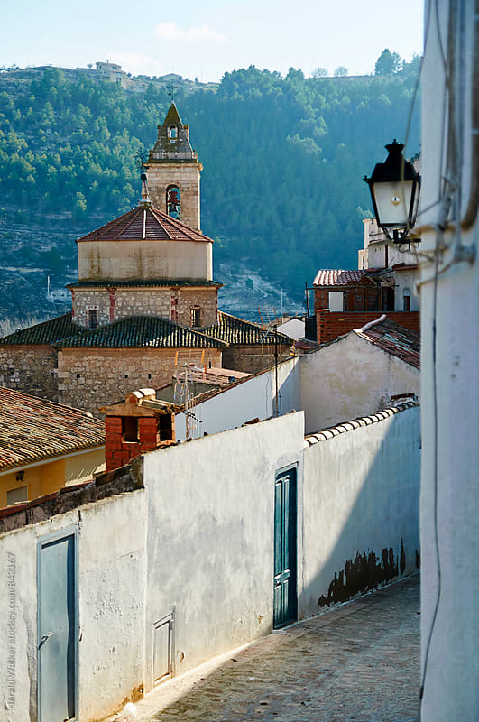 Alley in Alcala del Jucar with historic church by Harald Walker for Stocksy United