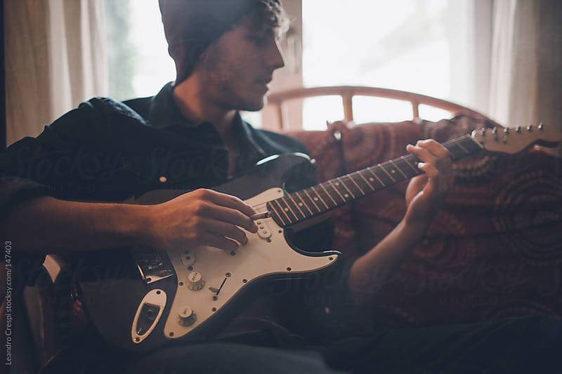 Man playing guitar by Leandro Crespi for Stocksy United